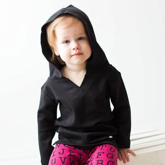 a little girl in a black hoodie
