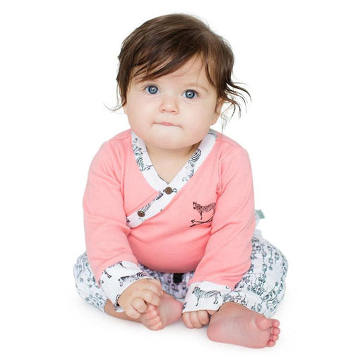 A baby wears a pink bodysuit and white pants
