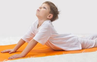 boy doing yoga on an orange mat