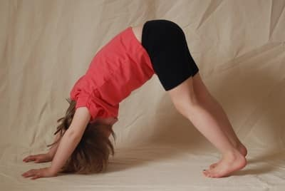 5 year old girl in pink t shirt and black shorts doing to downward dog yoga pose