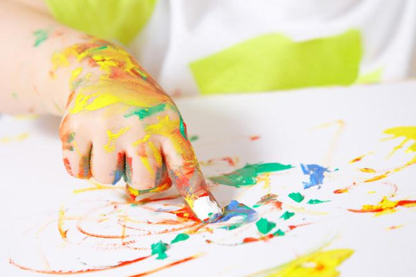 Child hand covered in many paint colours, using index finger to finger paint on white paper
