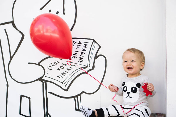 Baby sitting up holding a red balloon on a string in front of a white wall with black cartoon artwork in the background