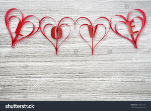 Background of gray wood grain background with red ribbons of love for Valentines Day lovers.