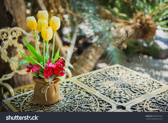 Beautiful spring bouquet of tulips on cast-iron table.