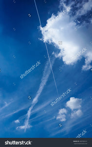 Fluffy, puffy white clouds and a contrail in a bright blue sky.