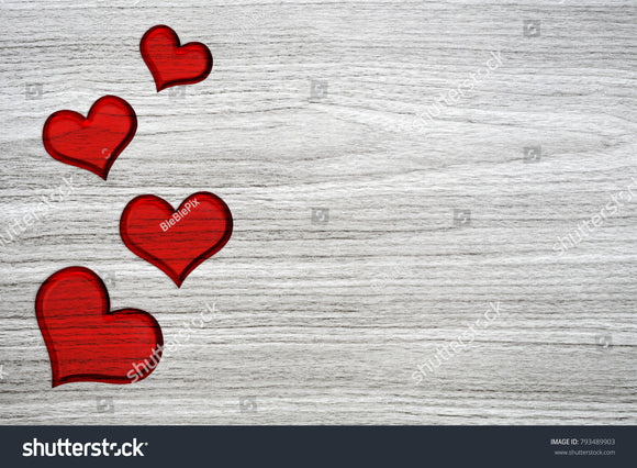 Red hearts of LOVE carving on a gray wood grain background.