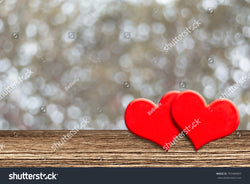 Two red hearts of LOVE on a light brown wooden table with lovely faded bokeh in the background.