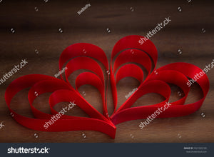 Vintage color style of red heart ribbons on a wood grain texture table with shadow lines.