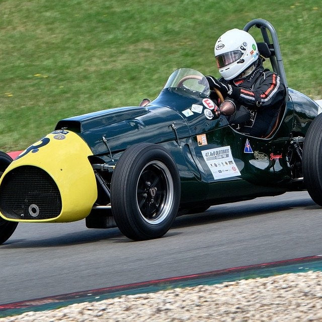 driver in racing suit driving a classic race car