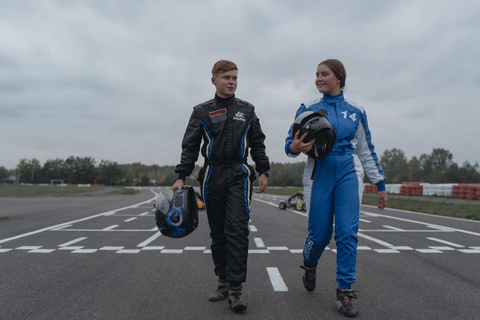 Two people on the racing track wearing racing suits, carrying their helmets
