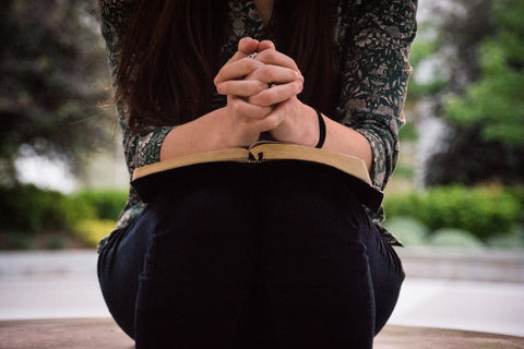 a girl with Bible on her knees praying