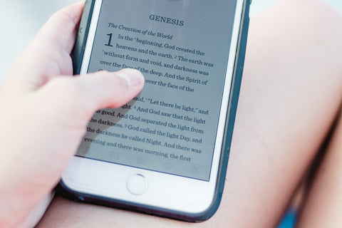 a person reading Genesis on the cellphone