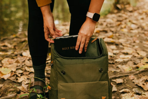 a person packing a bible in the backpack