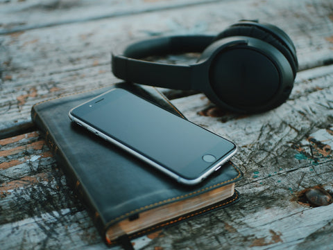 a mobile phone, The Bible with black cover and headphones on the wooden table