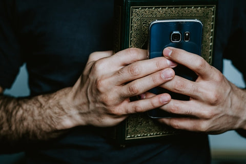 The Bible and the cellphone in person's hands
