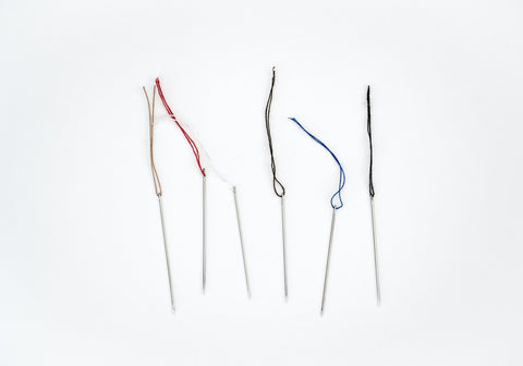 Six sewing needles with various colors of thread