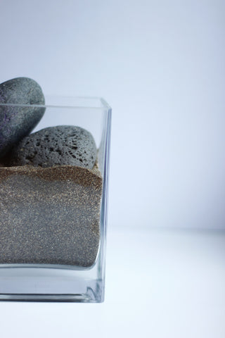 Square vase filled with sand and two stones
