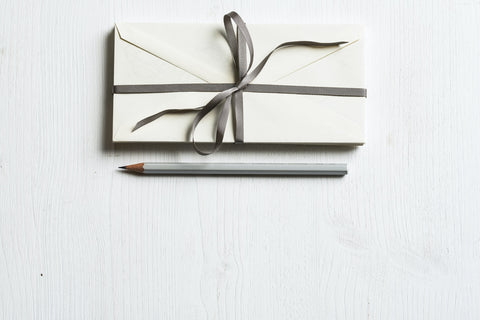 Envelopes tied together with ribbon and grey pencil