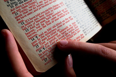 a finger pointing the words on the bible page