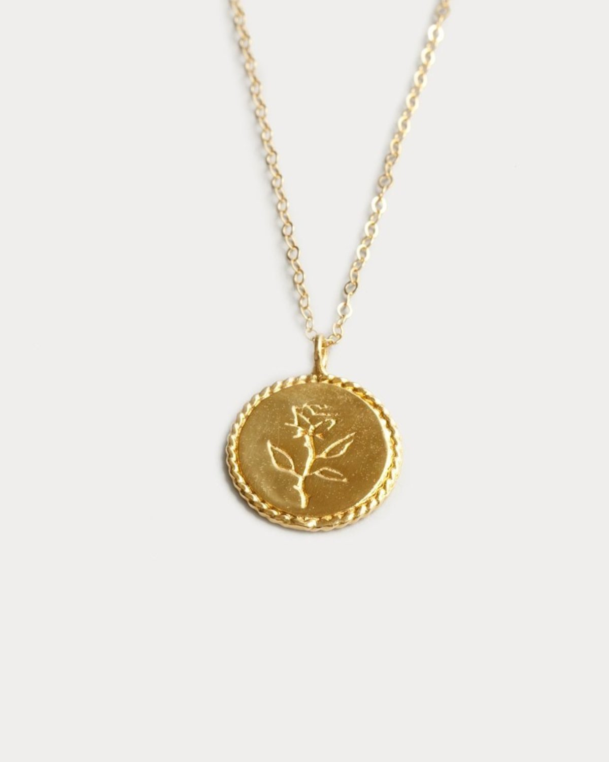 rose coin pendant in gold.
