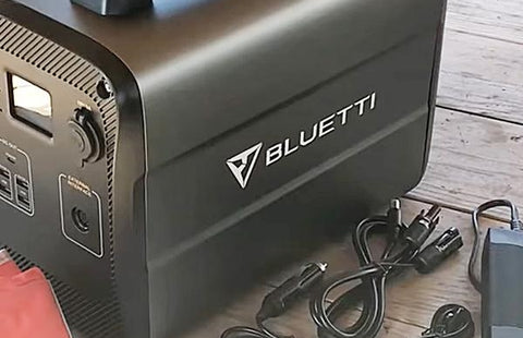Photo of Bluetti - AC100 1000Wh/600W Portable Power Station beside its charger.