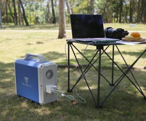 Photo of Bluetti - EB150 1500Wh/1000W Portable Power Station hooked in a laptop on the ground.