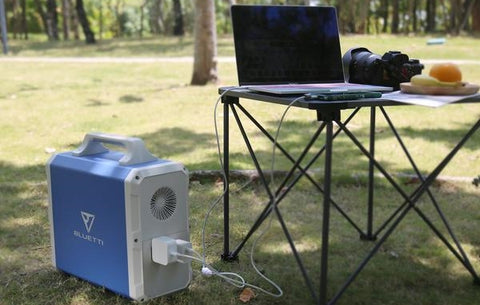 Photo of Bluetti - EB240 2400Wh/1000W Portable Power Station hooked in a laptop on the ground.