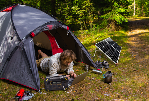 Photo of a man lying on his tent using his laptop hooked in Lion Safari Power Station.
