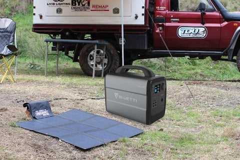 Photo of Bluetti - AC100 1000Wh/600W Portable Power Station beside a solar panel on a ground.