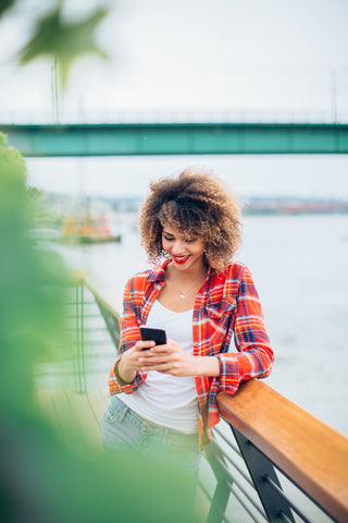 Woman with curly hair using her phone for self care apps