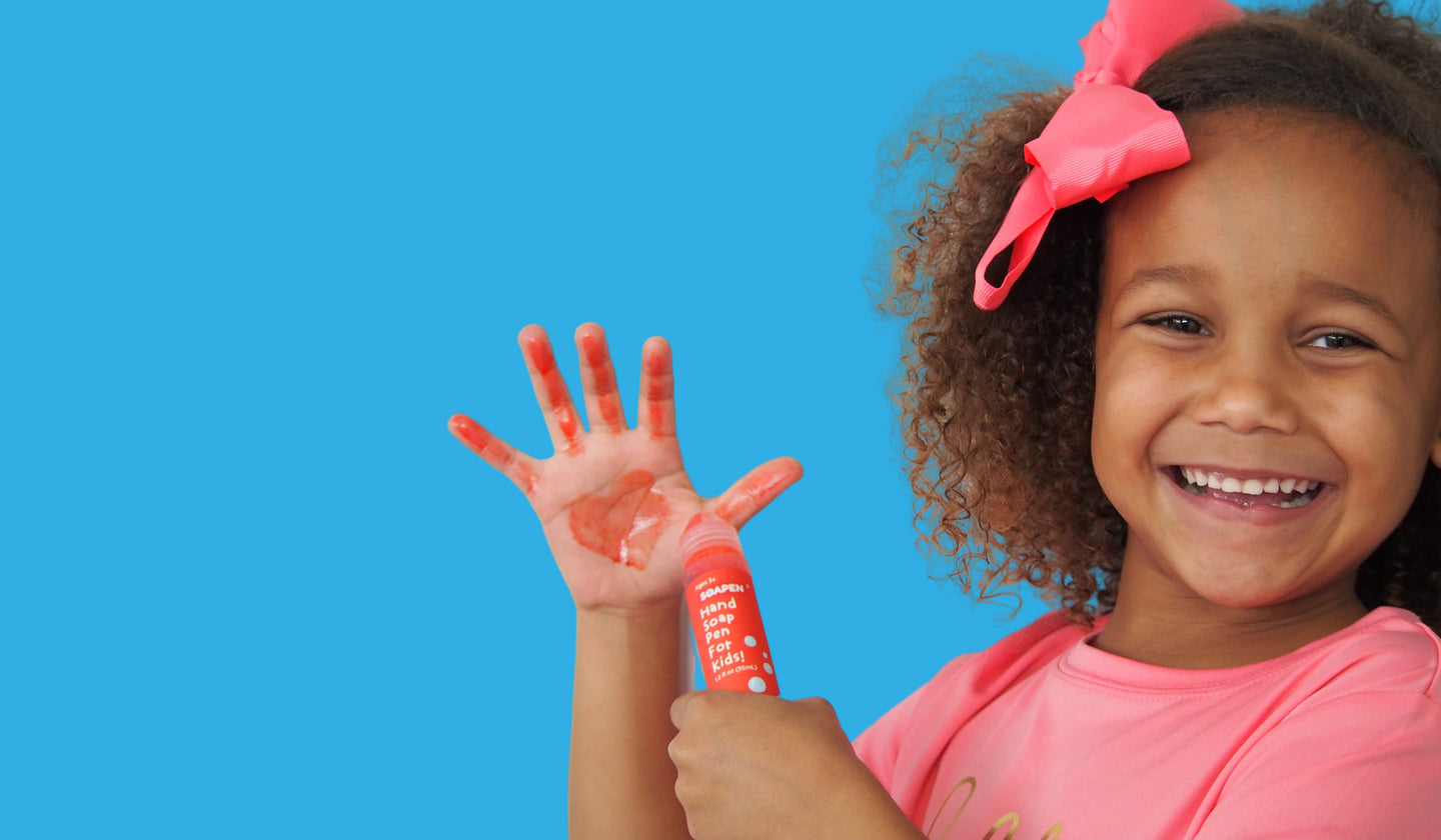 Little girl holding a SoaPen in her left hand and has a SoaPen orange drawing in the shape of a heart on her right hand