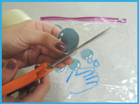 Cutting bubbles and excess packing tape around them.