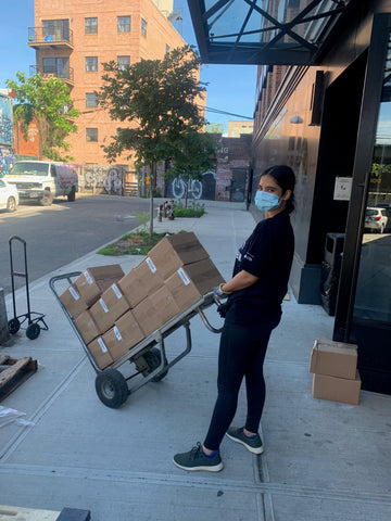 Boxes on a hand cart being moved by a woman
