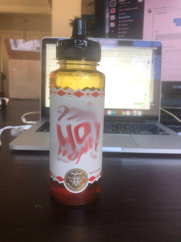 An image of a bottle with a flip cap and nozzle similar to a condiment bottle with the logo blurred out.