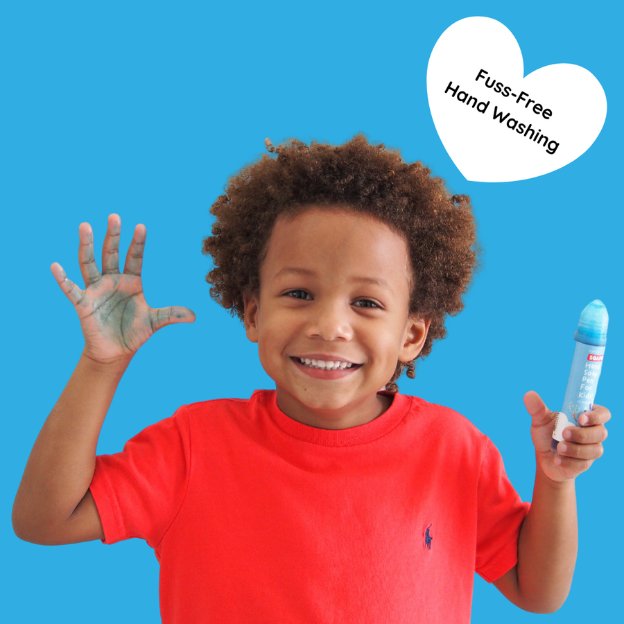 A little boy holding a SoaPen in his left hand and the SoaPen drawing on his right hand with a text in a heart saying