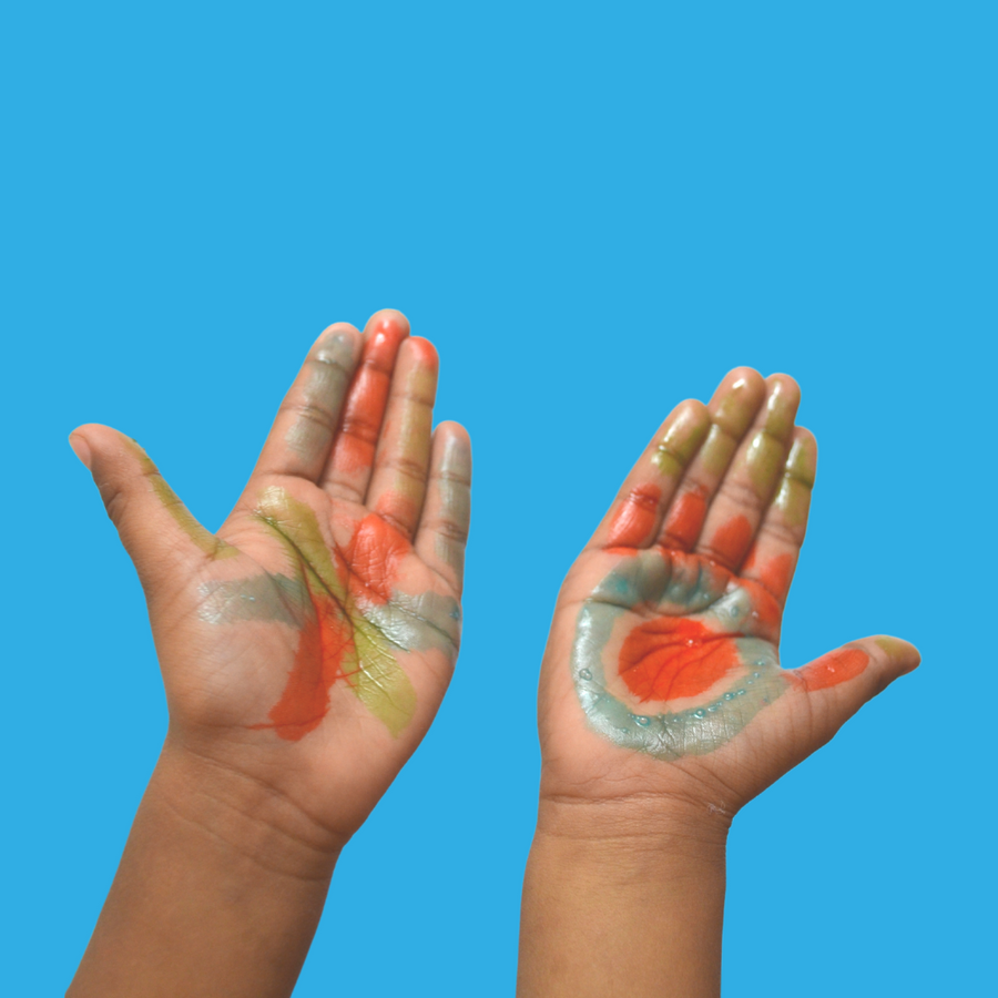 A kid's hands opened up and showing their SoaPen drawings on both palms