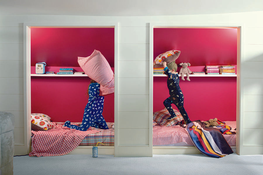 A kid's bedroom painted green and pink, showing two children having a pillow fight.