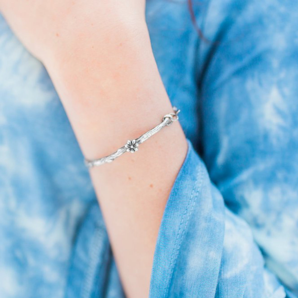 Branch Twig Bracelet with Cherry Blossom photographed on a model who is wearing a blue top