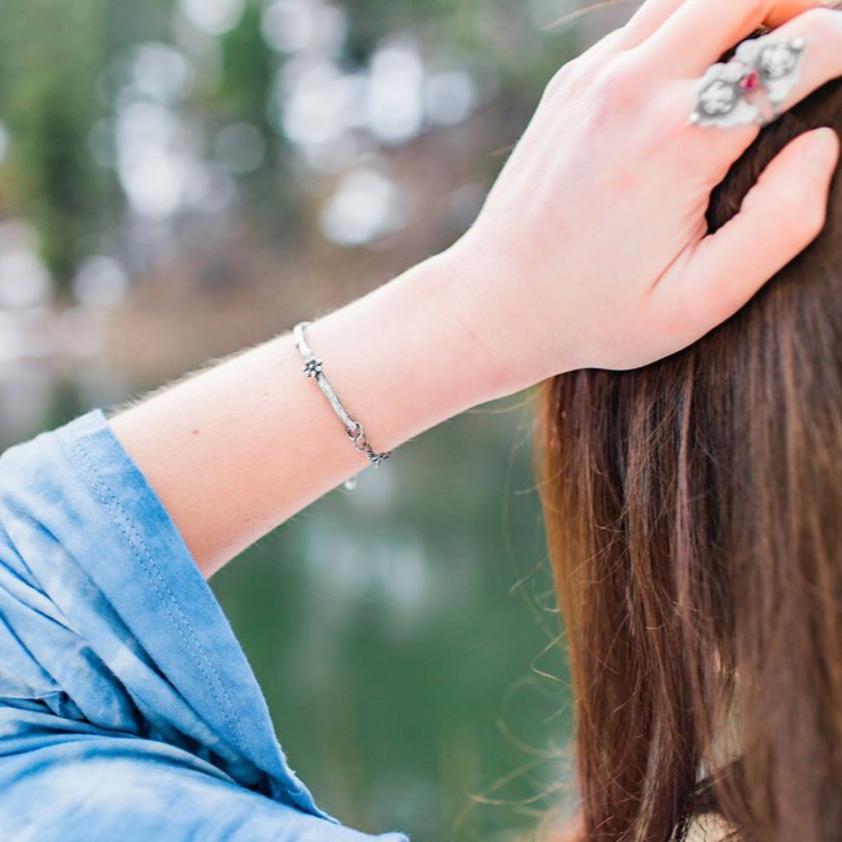 Branch Twig Bracelet with Cherry Blossom photographed on a model from behind with a lake scenery at the background