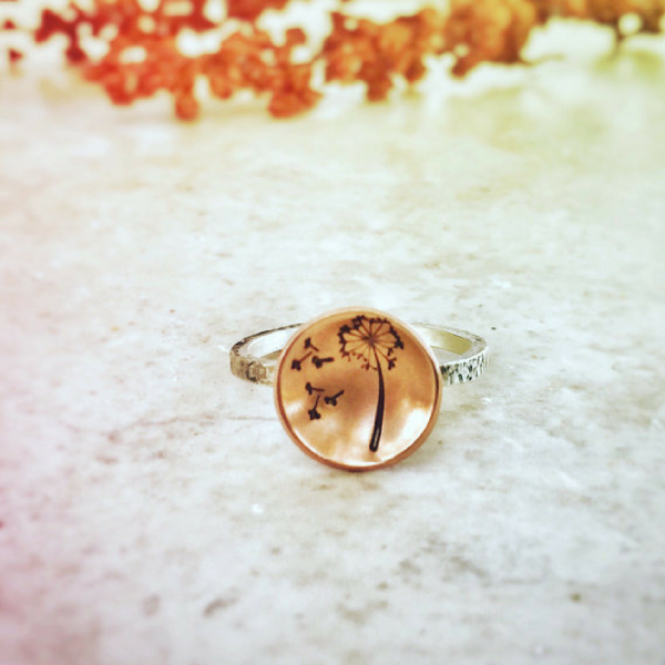 Dandelion Wish Ring with Copper and Silver front view laid on a marble and there is orange color flowers at the back ground that matches the ring