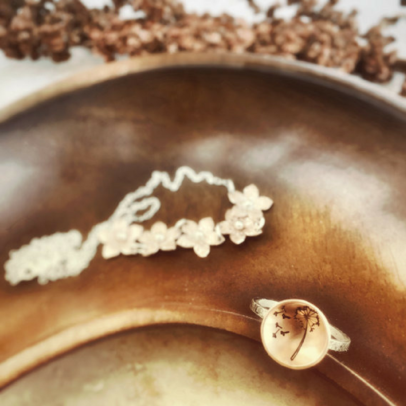 Dandelion Wish Ring with Copper and Silver in a jewelry dish photographed from top with another floral necklace design