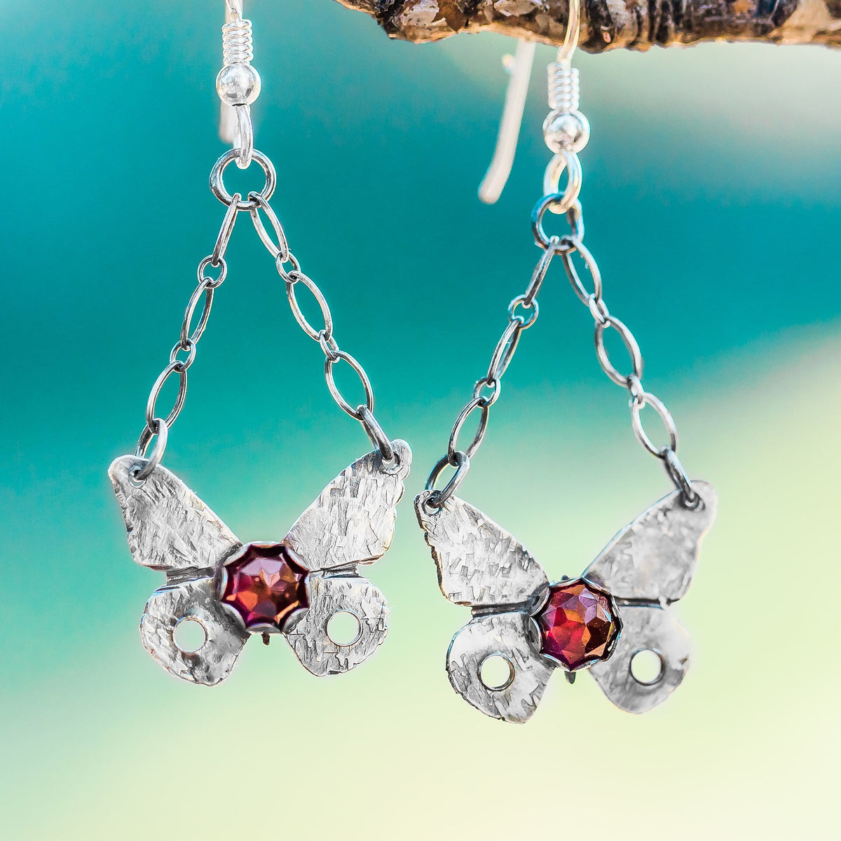 Sterling Silver Butterfly Earrings with Garnet Gemstone hang on a branch