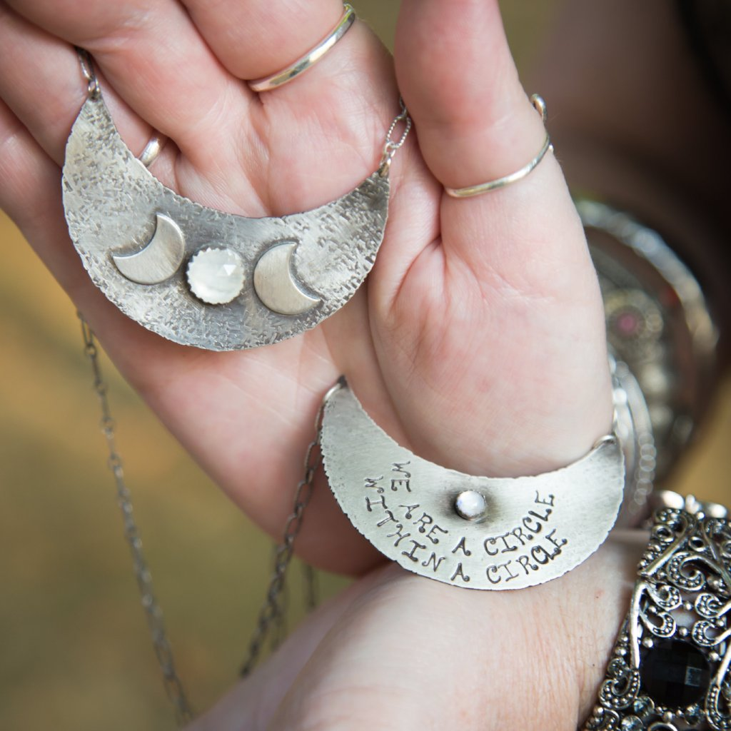 Triple Moon Goddess Necklace with Moonstone in hands of a model holding both of the necklaces showing each side of the pendant