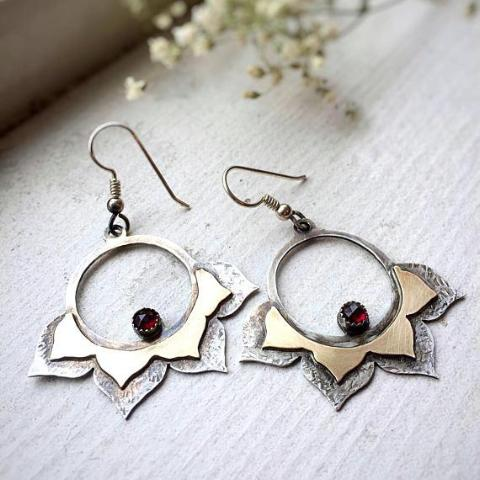 Lotus Hoop Earrings with Garnet photographed laid flat next to the window, there is some flowers at the background