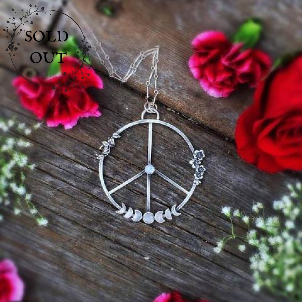 Moon Phases Peace Necklace with Moonstone laid flat on a wooden background surrounded with red roses and flowers