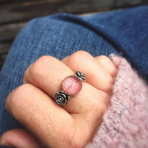 Pink Strawberry Quartz Flower Ring photographed on a finger, the model is wearing a pink cardigan shirt and jeans