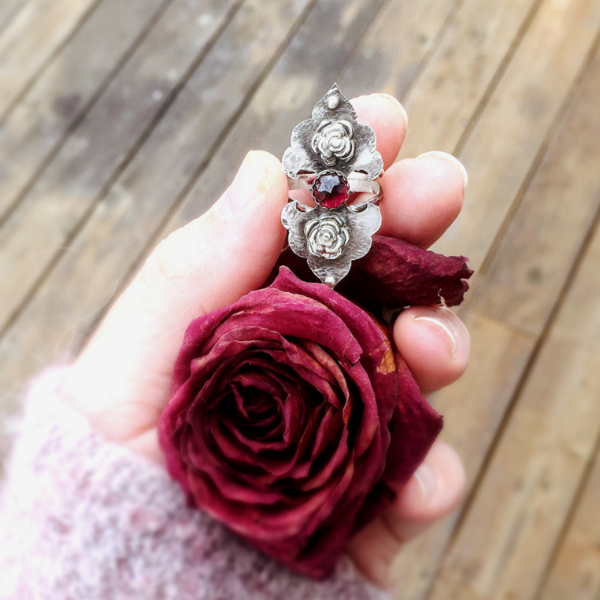 Rosebuds Flower Statement Ring with Garnet front view held in hand with a dried red rose