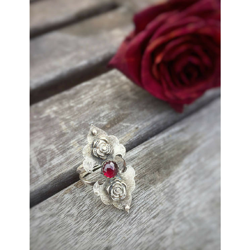 Rosebuds Flower Statement Ring with Garnet slightly side view with a dried red rose in the scene