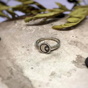 Moon and Star Celestial Ring front view laid on a stone with dried leaves at the background