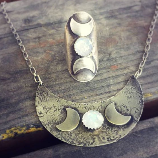 Triple Moon Goddess Necklace with Moonstone flat on a table with the triple moon goddess ring matching pair